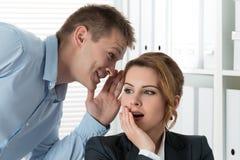 Junger Mann, der seiner Arbeitskollegin Klatsch sagt Stockfotos
