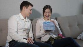 Junger Mann, der seiner Freundin Valentinsgrußgeschenkbox und Blumenstrauß von roten Rosen gibt stock footage