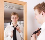 Junger Mann, der seins Gleichheit bindet Stockbilder