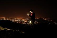 Junger Mann, der selfie auf den Hügel nimmt, die Nachtstadtansicht beobachtend Stockfotografie