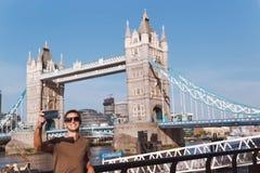 Junger Mann, der selfie in London mit Turm-Brücke auf Hintergrund nimmt lizenzfreie stockfotos