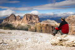 Junger Mann, der Sella-Gruppenberg vom Sass Pordoi, Dolomit, Italien betrachtet lizenzfreie stockfotografie