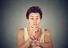 Junger Mann, der Shhhh ruhige Ruhegeheimnisgeste gibt Stockbild