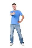 Junger Mann, der sich Daumen zeigt Stockfoto