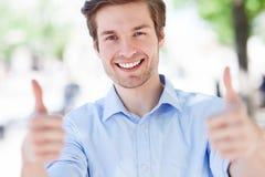 Junger Mann, der sich Daumen zeigt Stockbild