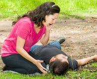 Junger Mann, der sich mit medizinischem Notfall, Frau sitzt durch seine Seite ruft um Hilfe, draußen Umwelt hinlegt lizenzfreies stockfoto