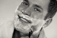 Junger Mann, der sich mit Sahne unter Verwendung des Schaums des Rasiermessers rasiert Stockfotografie