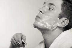 Junger Mann, der sich mit Sahne unter Verwendung des Schaums des Rasiermessers rasiert Lizenzfreie Stockfotografie