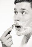 Junger Mann, der sich mit Sahne unter Verwendung des Schaums des Rasiermessers rasiert Stockfotos