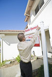 Junger Mann, der sich setzt herauf 'für Verkaufs-Mitteilung' Stockbild