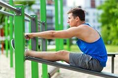 Junger Mann, der SitzenUPS Turnhalle an der im Freien tut Stockbilder