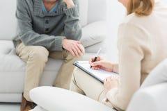 Junger Mann in der Sitzung mit einem Psychologen Stockbild
