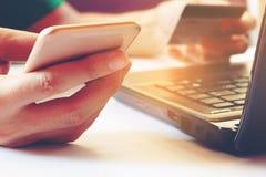 Junger Mann, der Smartphone verwendet und Kreditkarte mit Laptop f hält Stockfotos