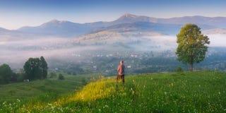Junger Mann, der Sonnenaufgang im Bergdorf genießt Lizenzfreies Stockfoto