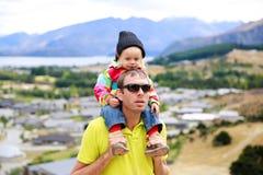 Junger Mann in der Sonnenbrille mit einem kleinen Mädchen auf seinen Schultern Irgendwo in Neuseeland Stockbild