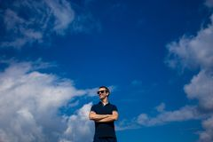 Junger Mann in der Sonnenbrille steht gegen den blauen Himmel Stockbild