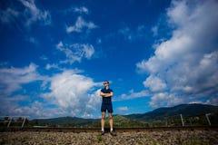 Junger Mann in der Sonnenbrille steht gegen den blauen Himmel Stockfoto