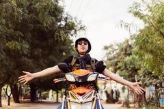 Junger Mann in der Sonnenbrille und im Sturzhelmreitmotorrad, das oben Hände als Sieger und Erfolg anhebt lizenzfreies stockfoto
