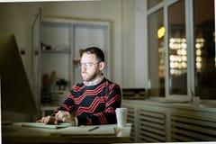 Junger Mann, der spät im Büro arbeitet lizenzfreie stockfotos