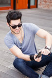 Junger Mann, der Spiele auf einem smartphone spielt Stockbilder