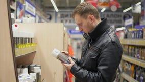 Junger Mann, der Sprühfarbe im Färbungsshop wählt Reihen von Regalen mit Farbendosen Er rüttelt einen Kanister und betrachtet stock video footage
