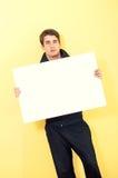 Junger Mann in der Spurklage, die unbelegte weiße Karte anhält stockfoto