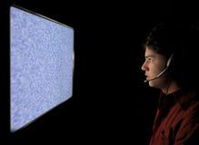 Junger Mann, der in statischen Fernsehbildschirm anstarrt Lizenzfreie Stockfotos
