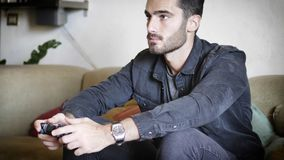 Junger Mann, der Steuerknüppel oder joypad für Videospiele verwendet stockfotografie