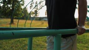 Junger Mann, der StoßUPS vom Barren auf dem Spielplatz in einem natürlichen allgemeinen Park tut stock video