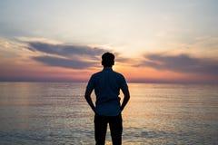 Junger Mann, der am Strand vor erstaunlicher Seeansicht bei Sonnenuntergang oder Sonnenaufgang steht und an seine Zukunft denkt r Stockfotos