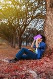 Junger Mann in der Stresssituation, wenn ein Buch im Park gelesen wird lizenzfreie stockbilder