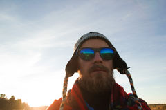 Junger Mann in der Strickmütze, in der Sonnenbrille und in der Decke auf dem Hintergrund eines Feldes und des blauen Himmels Lizenzfreie Stockfotos