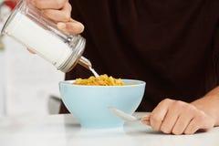 Junger Mann, der Sugar To Breakfast Cereal addiert Stockbild