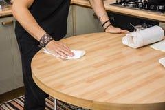Junger Mann, der Tabelle mit Papierhandtuch in der Küche abwischt Lizenzfreie Stockfotografie