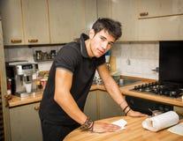 Junger Mann, der Tabelle mit Papierhandtuch in der Küche abwischt Stockfotos