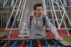 Junger Mann, der tablefootball spielt und ein Ergebnis im Park in Moskau ändert stockbild