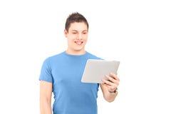 Junger Mann, der Tablette steht und betrachtet Stockfoto