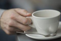 Junger Mann, der Tasse Kaffee innerhalb der Kaffeestube hält Lizenzfreies Stockfoto