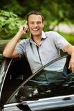 Junger Mann, der am Telefon über Auto spricht Stockfotos