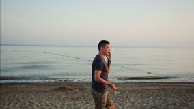 Junger Mann, der am Telefon auf dem Strand spricht stock video footage