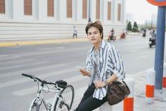 Junger Mann, der Telefon beim Sitzen mit Fahrrad im Park verwendet Stockfotos