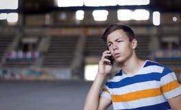 Junger Mann, der am Telefon im Altbau spricht Stockfotografie