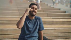 Junger Mann, der am Telefon sitzt auf Treppe am sonnigen Tag spricht stock footage