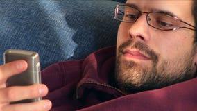 Junger Mann, der an Telefon sms lächelt stock video