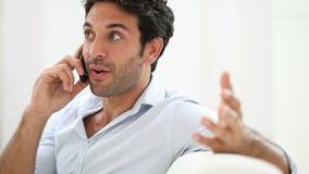 Junger Mann, der am Telefon spricht stock footage