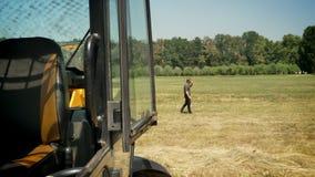 Junger Mann, der am Telefon spricht und auf Strohfeld, hinter Traktor, Landschaft, besetzt geht stock video