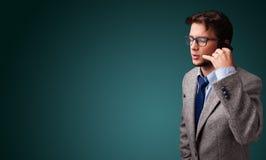 Junger Mann, der Telefonanruf mit Kopienraum macht Stockfoto