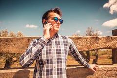 Junger Mann, der telefonisch in der Landschaft spricht Stockbild