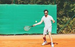 Junger Mann, der Tennis auf der öffentlichen Sitzung spielt Lizenzfreie Stockfotografie