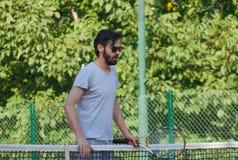 Junger Mann, der Tennis auf der öffentlichen Sitzung spielt Lizenzfreie Stockfotos